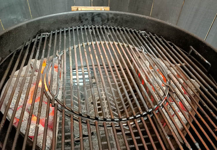 weber kettle with two charcoal baskets on each side of the grill