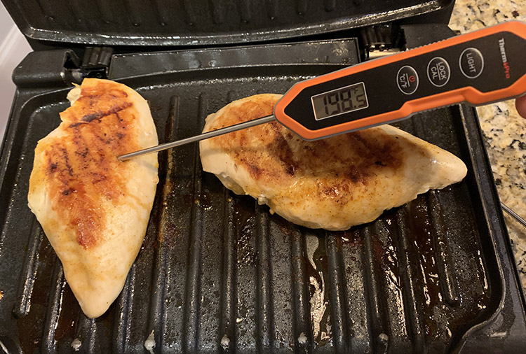 chicken breasts on a grill with ThermoPro TP15H digital instant read meat thermometer