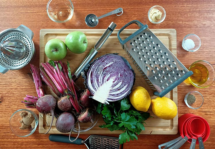 apples, beets, lemons and other slaw ingredients on a wooden board