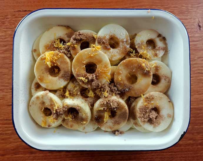 apple slices sprinkled with sugar, cinnamon, maple syrup and lemon zest