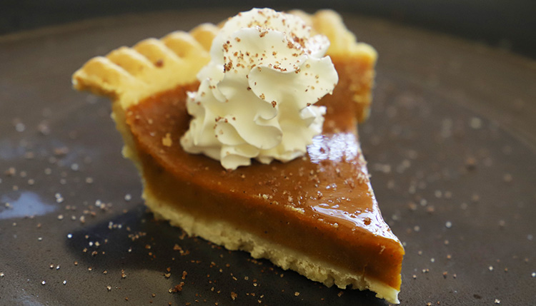 a slice of smoked pumpkin pie with whipped cream on top