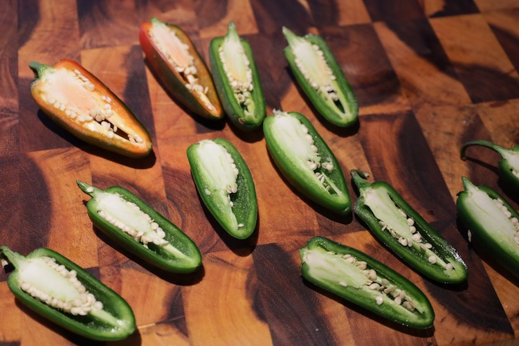 jalapeno peppers sliced in half on a wooden board
