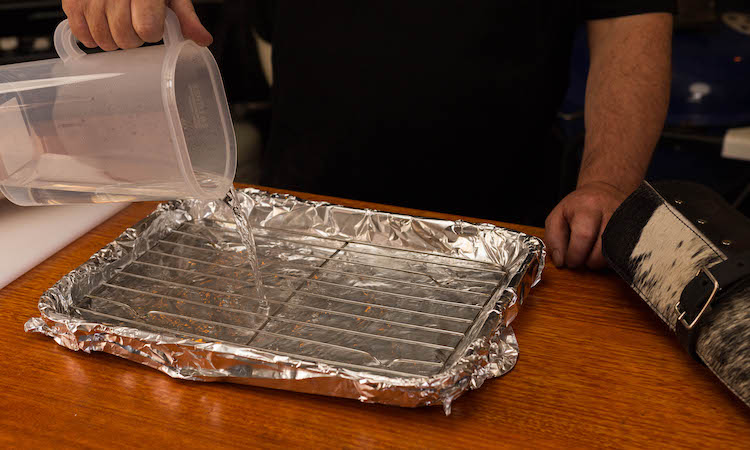 pouring water into a baking pan covered with foil