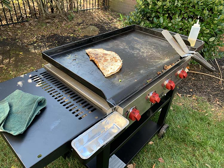 Camp Chef Flat Top Grill with side tables and food cooking on a griddle