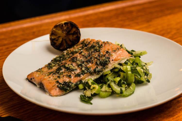 Cedar planked salmon and celery parmesan salad on a plate