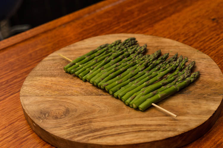 asparagus threaded on a skewer on a wooden board