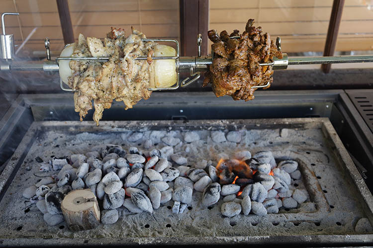 sliced chicken and lamb shoulder cooking on a rotisserie rod with charcoal burning underneath