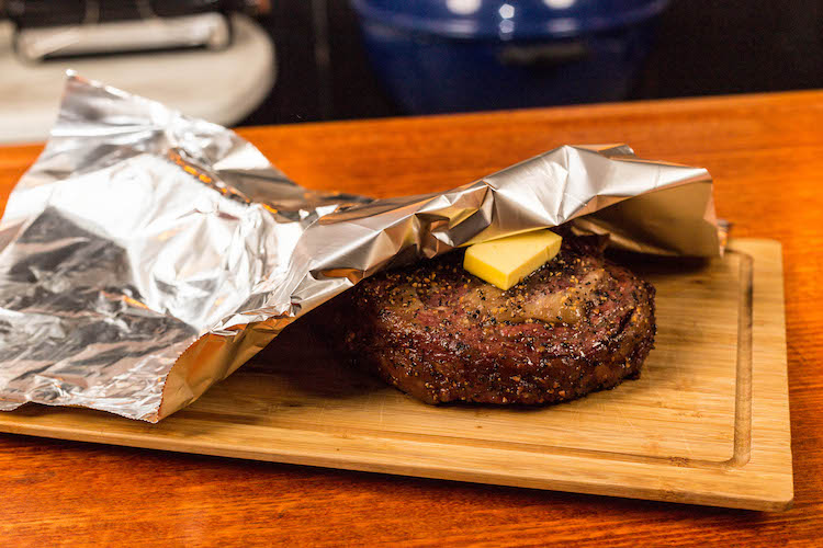 tomahawk steak and a piece of butter covered in foil