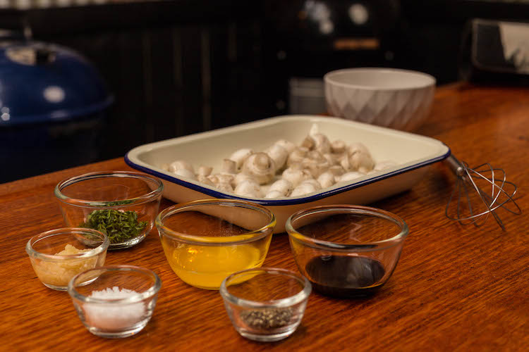 white button mushrooms in a baking tray and garlic butter seasoning ingredients