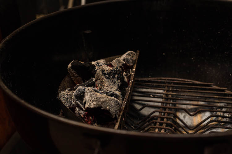 lump charcoal placed on one side of the grill