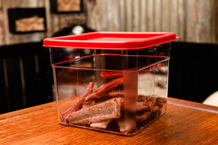 seasoned lamb ribs in a plastic container