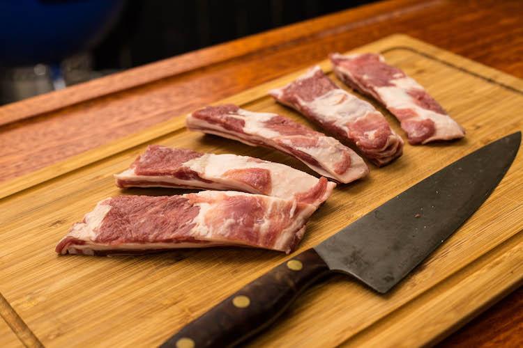 raw lamb ribs on a wooden board