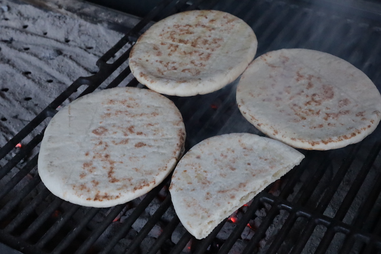 pieces of pita bread heating up on a grill