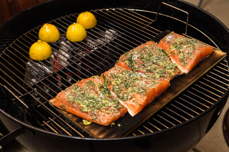 seasoned salmon fillets and halved lemons on a grill