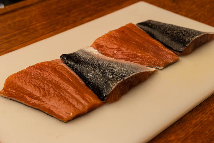 salmon fillets on a plastic board