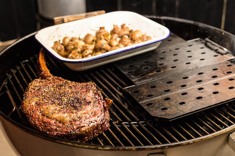 tomahawk steak and white button mushrooms on a Weber kettle grill