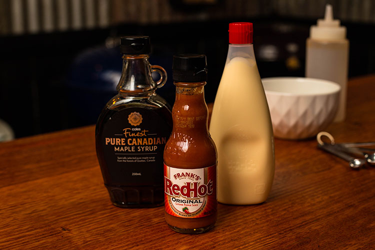 maple syrup, hot sauce and Kewpie mayonnaise bottles on a wooden table