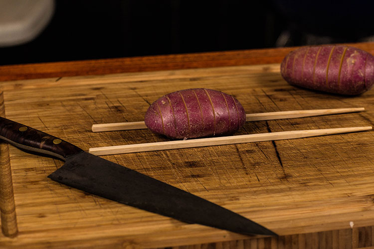 uncooked potatoes with chopsticks on a wooden cutting board