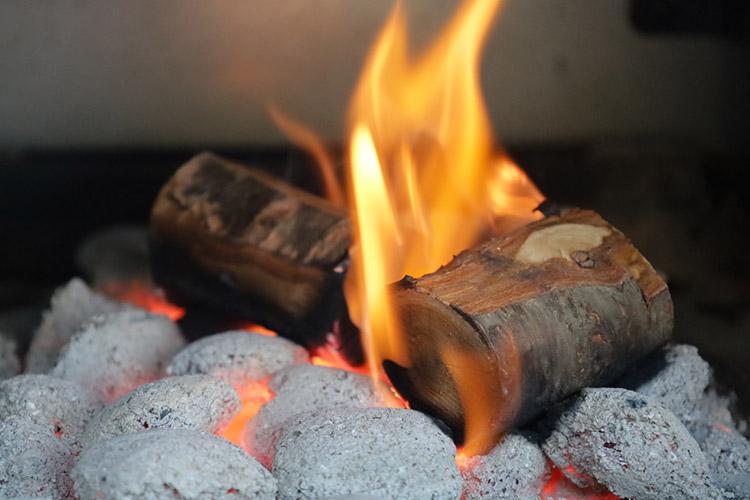 pecan wood chunks burning on top of charcoal