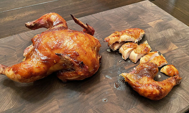 smoked cornish game hens on a wooden board