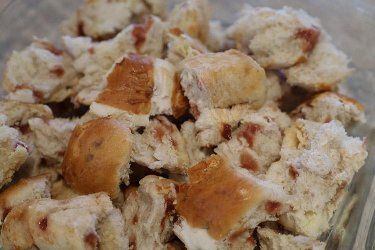 torn hot cross buns in a glass dish