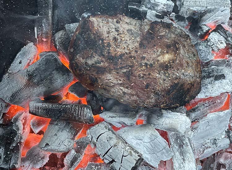 cooked caveman ribeye steak on hot lump charcoal
