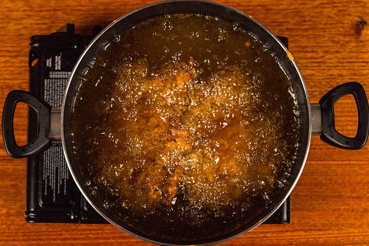 chicken thighs frying in oil in a frying pan