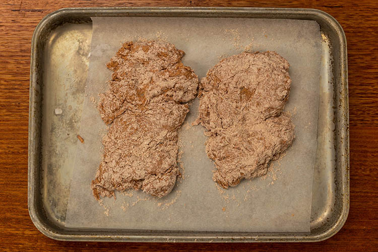 chicken thighs covered in breading on a metal tray