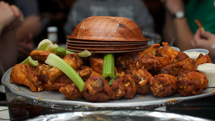 a plate of buffalo wings and celery