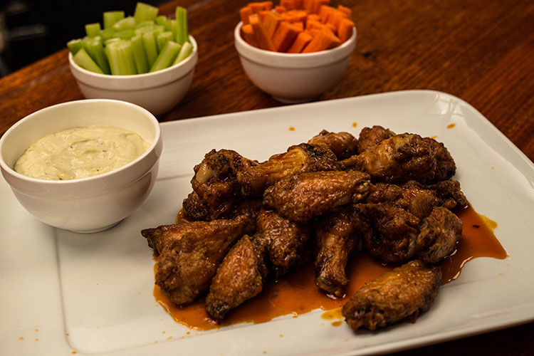 buffalo wings with blue cheese sauce on a white plate