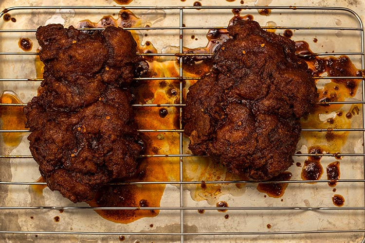 Fried Nashville Chicken covered in hot sauce on a wire rack