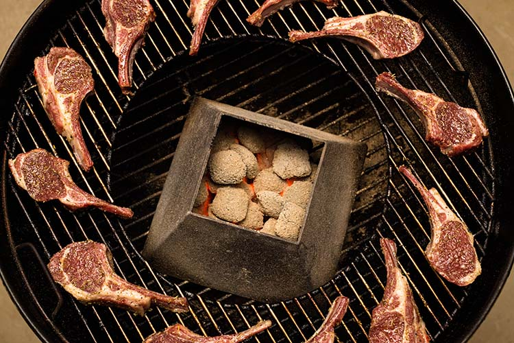 uncooked lamb cutlets on a weber kettle