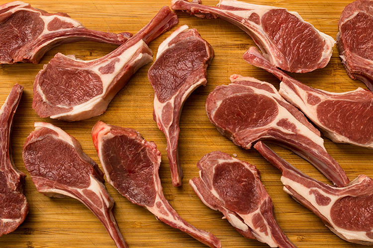 uncooked lamb cutlets on a wooden board