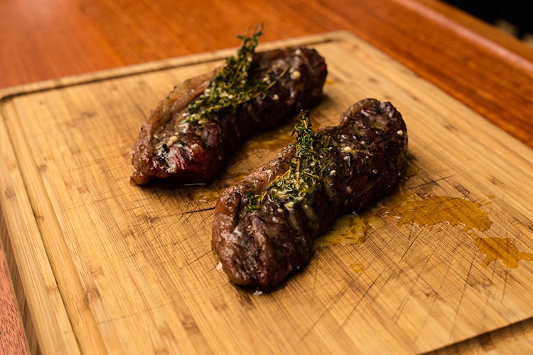 picanha steaks with thyme and butter on a wooden board