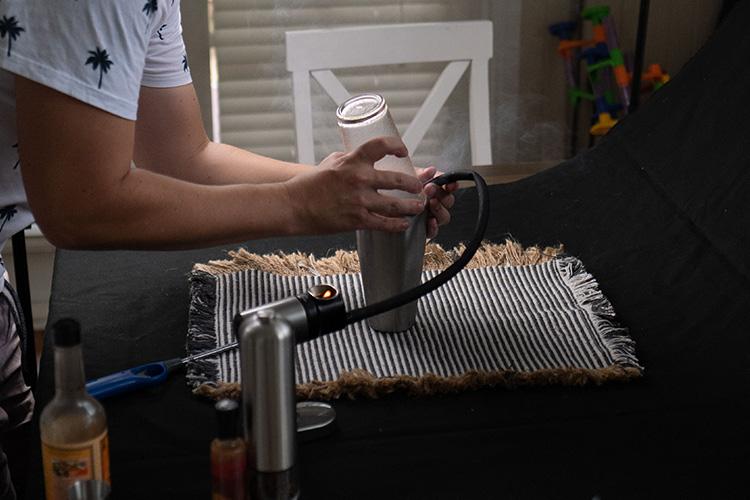 a process of adding smoke into a cocktail shaker using a smoking gun