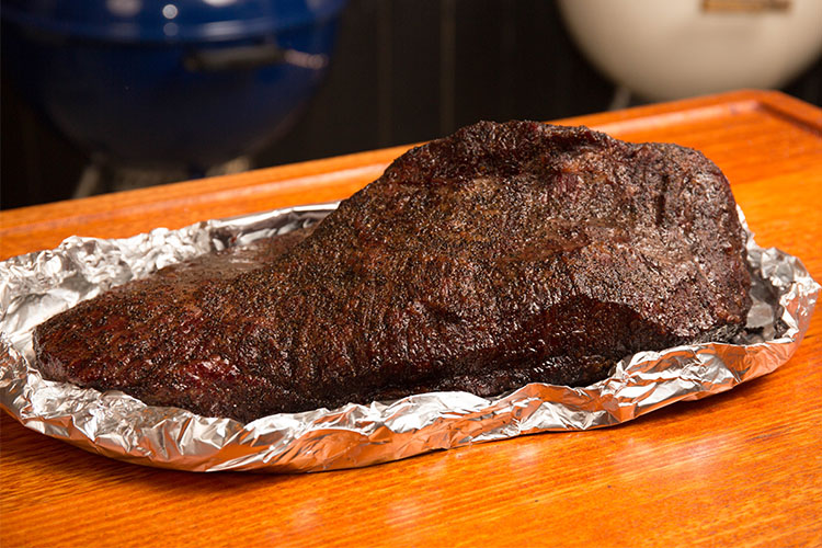 beef brisket boated in foil on a wooden table