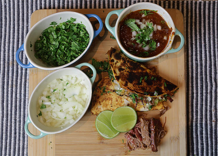 birria taco, consomme, chopped onions, cilantro and half of lime on a wooden board