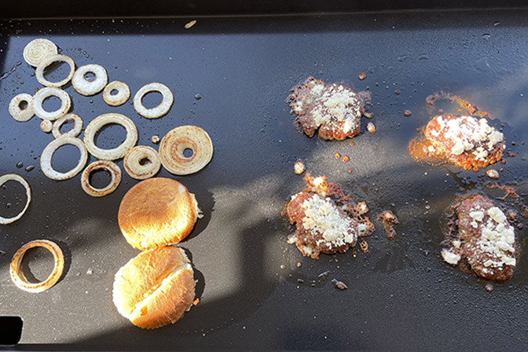 lamb burger patties with feta cheese, onion slices and brioche buns cooking on a griddle