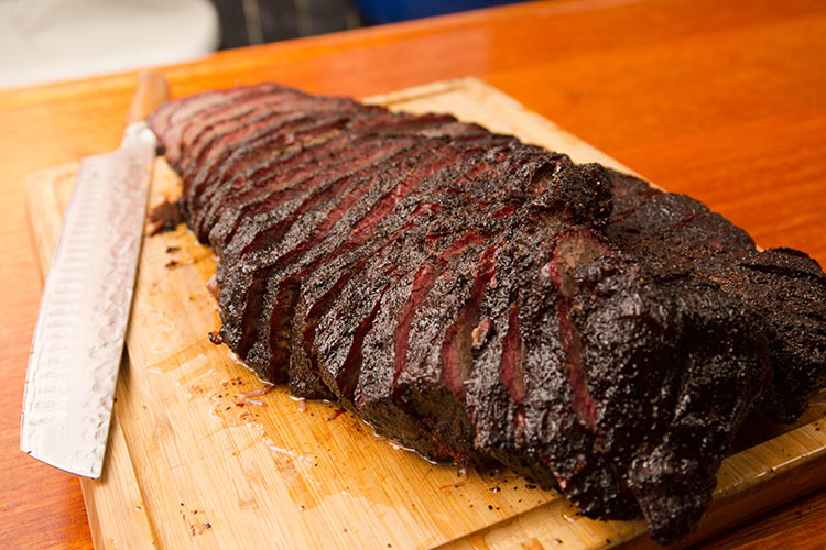 sliced hot and fast style brisket on a wooden board