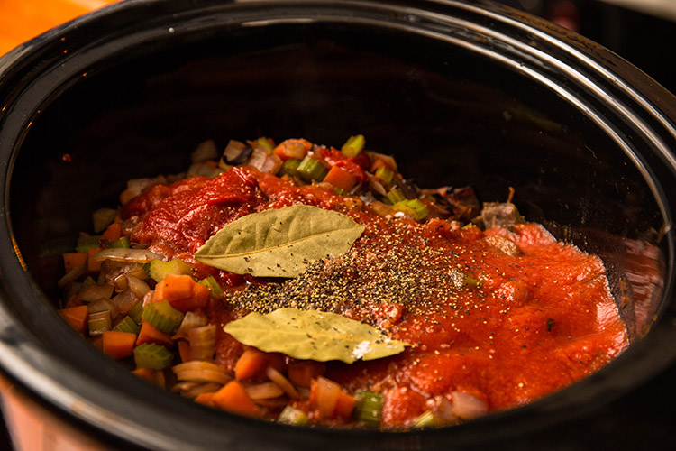 brisket, vegetables, tomato paste and bay leaves in a slow cooker