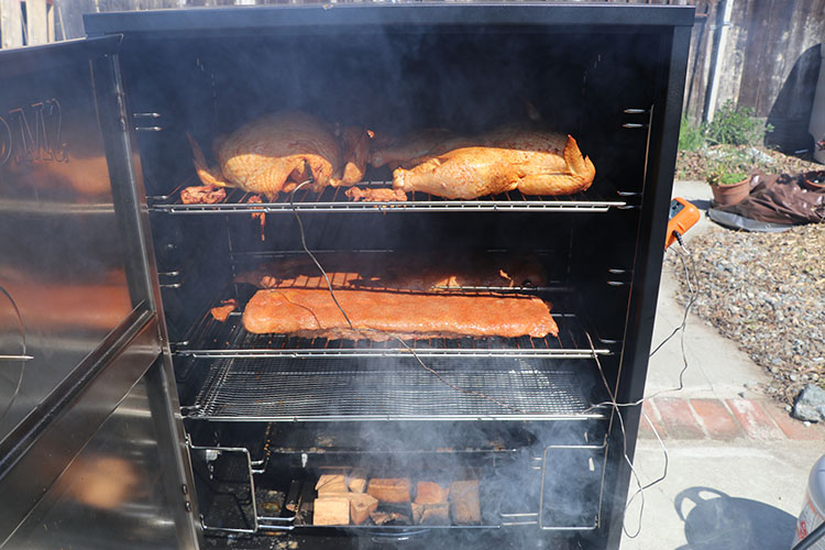 Whole chicken and pork ribs cooking on Camp Chef Smoke Vault