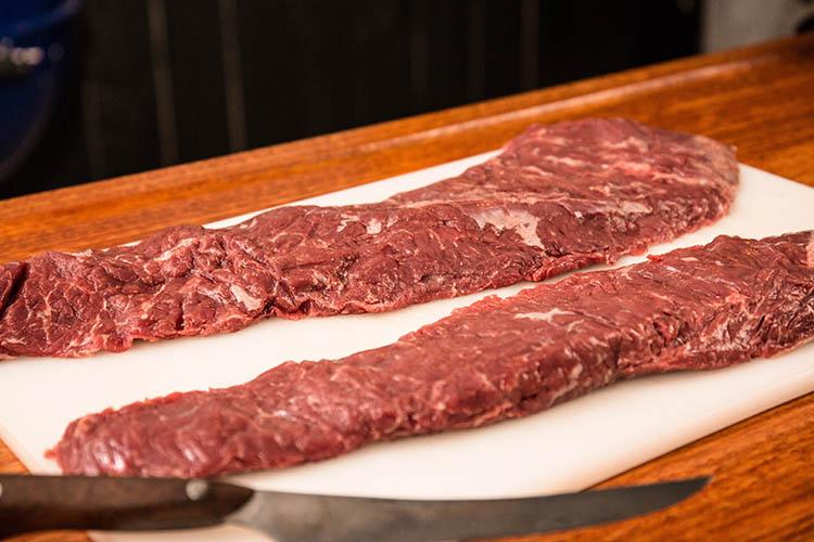 two skirt steaks on a plastic board