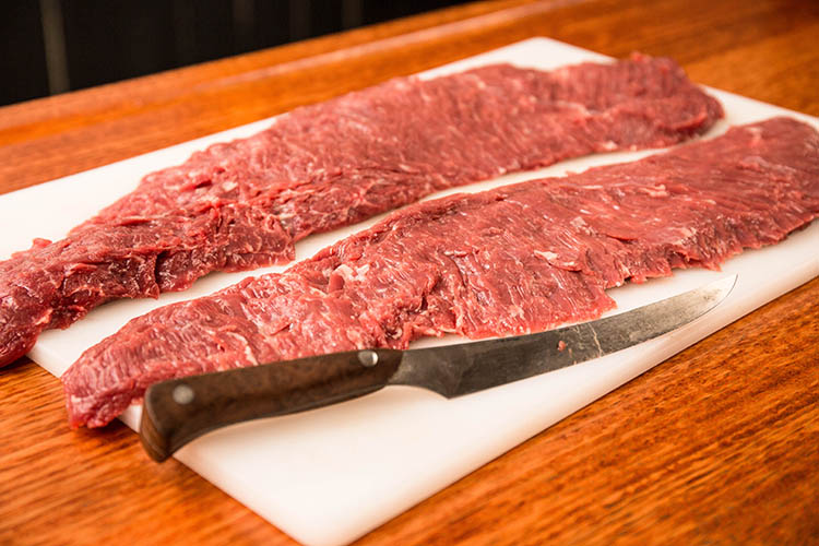 two skirt steaks without the silver skin on a plastic board