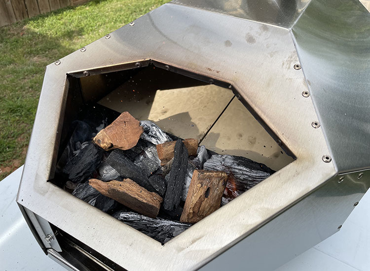 Ooni Pro 16 fuel hatch with lump charcoal and wood chunks