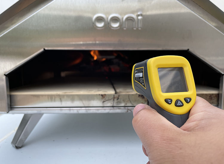 Ooni infrared thermometer pointing at Ooni Pro pizza oven