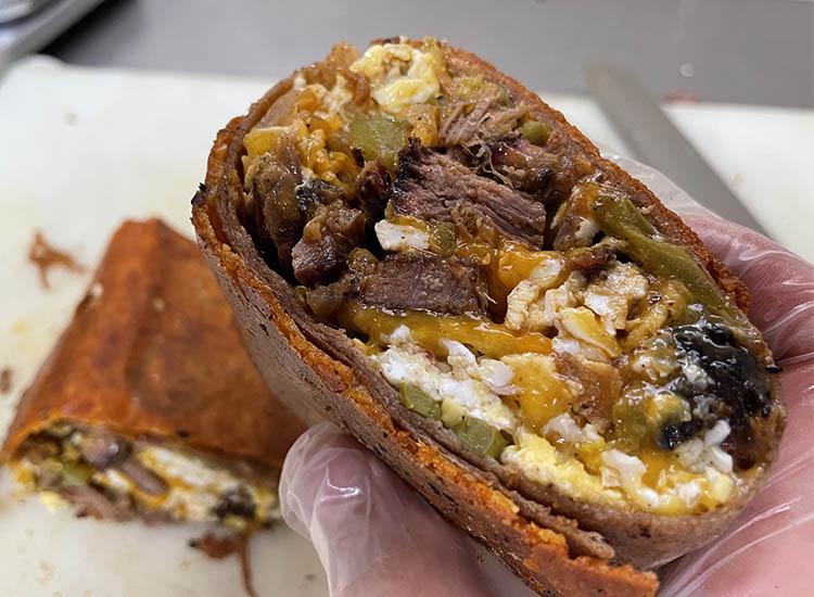a man holding a half of brisket breakfast burrito