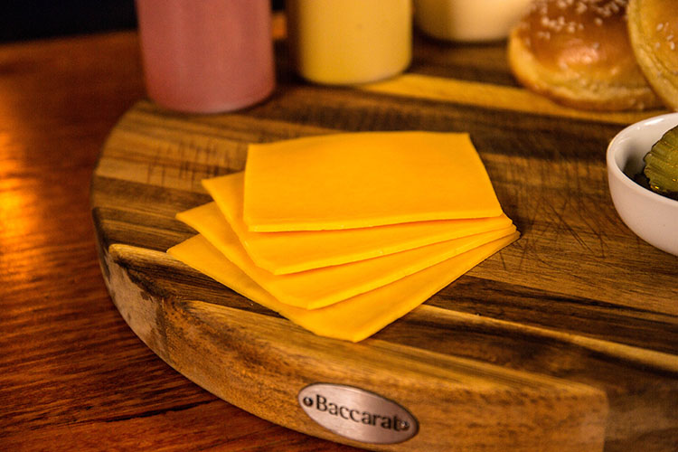 sliced cheddar cheese on a wooden board