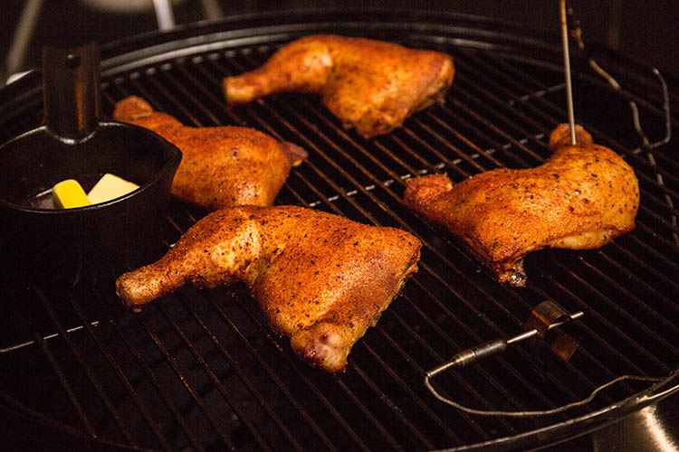cast iron pan and chicken legs on a smoker