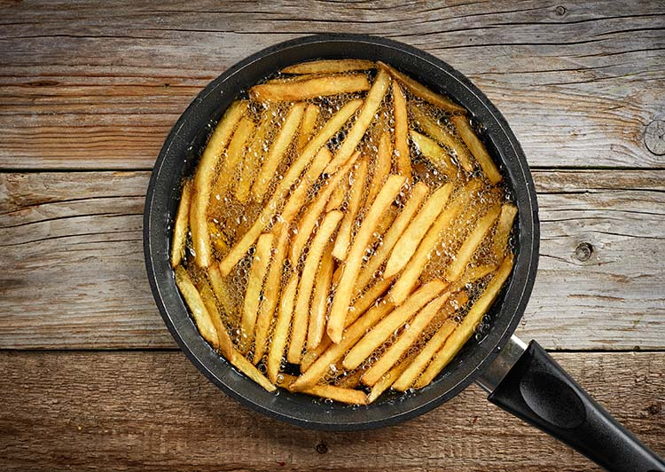 frying french fries in a pan with oil