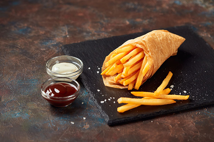 french fries with sauces on slate cutting board